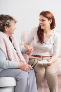 Happy caregiver talking with smiling senior woman while visit he